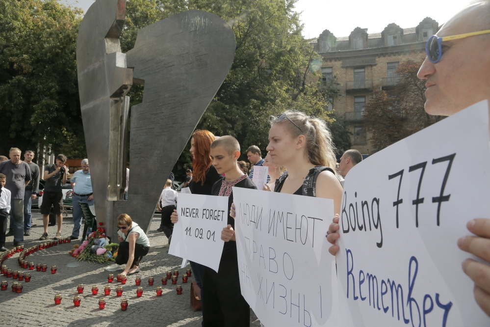 Ukrainians hold posters during a remembrance ceremony in memory of the Sept. 11 terror attacks  in the United States and memory of the people, who died during the Boeing 777, Malaysia Airlines flight MH17 crash in eastern Ukraine at the monument of victims of terror in Kiev.