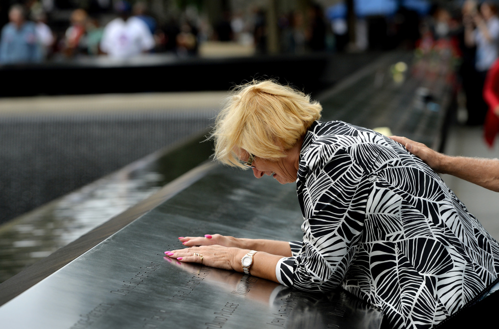 Paola Braut of Belgium cries over a photograph of her son Patrice along the edge of the North Pool during memorial observances on the 13th anniversary of the Sept. 11 terror attacks on the World Trade Center in New York.