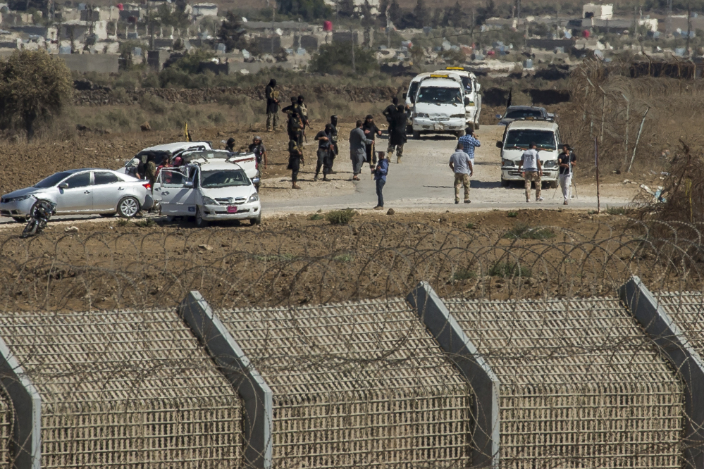 Al-Qaida-linked Syrian militants gather around vehicles carrying U.N. peacekeepers from Fiji before releasing them, as they arrive near the Syrian village of Al Rafeed in Syrian-controlled side of the Golan Heights on Thursday.
