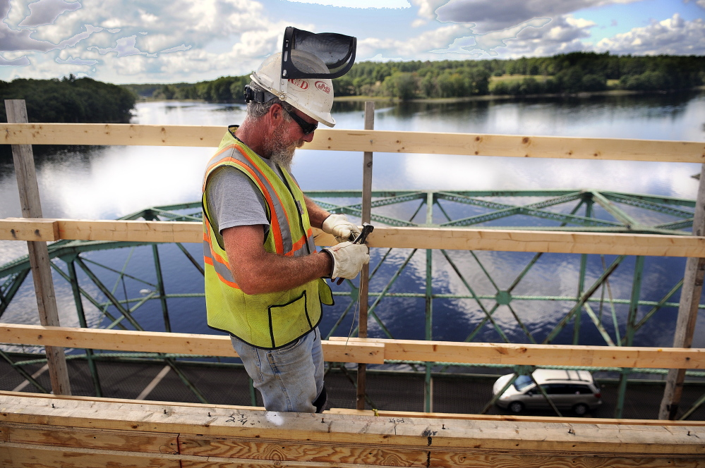 Reed & Reed Inc. worker Bob St. Pierre clips a piece of wire Wednesday to secure reinforcing steel on the deck of the new bridge the firm is constructing over the Kennebec River between Richmond and Dresden. Tom Reed, who is overseeing the project for the Woolwich company, said he hopes to have the bridge open by Thanksgiving. Crews will then begin to disassemble the old swing bridge below.
