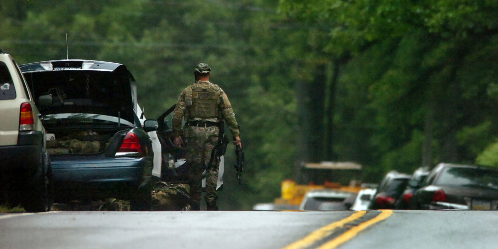 A member of the Pennsylvania State Trooper's Tactical Response Unit stands near his vehicle on Route 402 on Saturday near the scene where a Pennsylvania State Trooper was killed and another trooper was injured during a shooting late Friday night at the Pennsylvania State Police barracks in Blooming Grove Township, Pa.