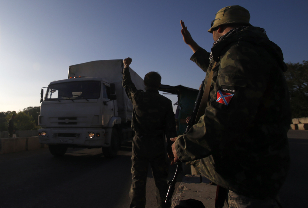 Pro-Russian rebels wave to trucks marked as Russian aid convoy to Ukraine as they return to Russia near the town of Krasnodon, eastern Ukraine, Saturday.