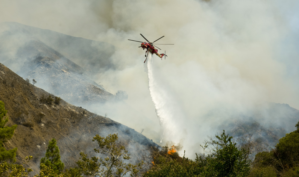 An Orange County Fire Authority helicopter drops a load of water on a brush fire in Silverado Canyon in Orange County, Calif. on Friday.