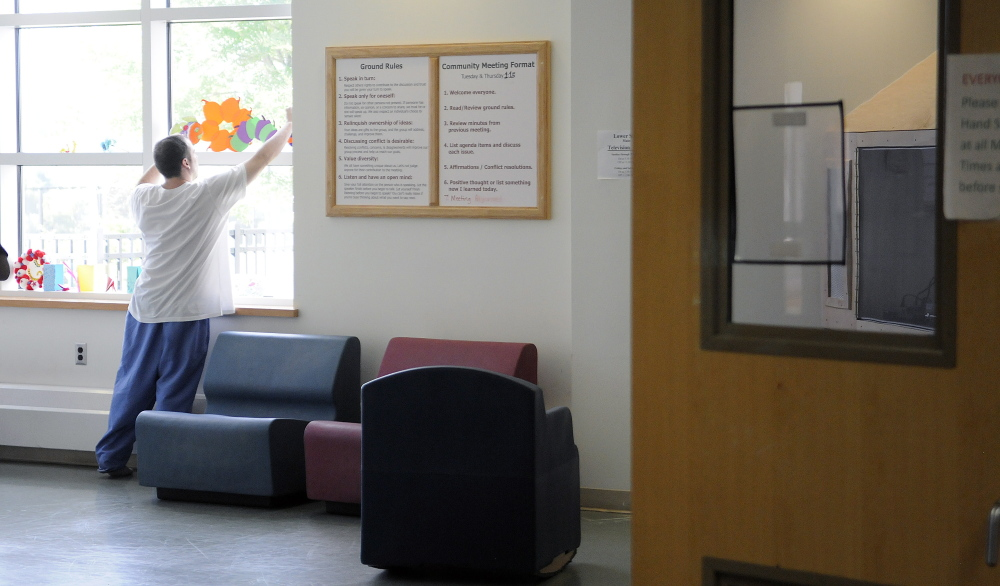 A patient hangs paper cutouts of pumpkins last week in the community room at the Lower Saco forensic unit at Riverview Psychiatric Center in Augusta.