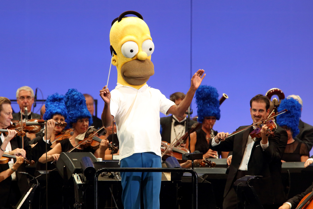 "In this photo provided by the Hollywood Bowl, the orchestra, led by conductor Thomas Wilkins in a Homer Simpson costume, performs at the world premiere of ""The Simpsons Take the Bowl"" at the legendary concert venue Friday in Los Angeles."