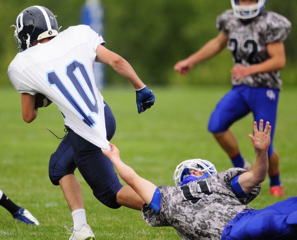 Dirigo halfback Joe Casey gets snagged by Oak Hill defensive back Jonah Martin Saturday at Oak Hill High School in Wales. The Cougars beat the Raiders 14-6, snapping an eight-game winning streak for Oak Hill, the longest active streak in the state.