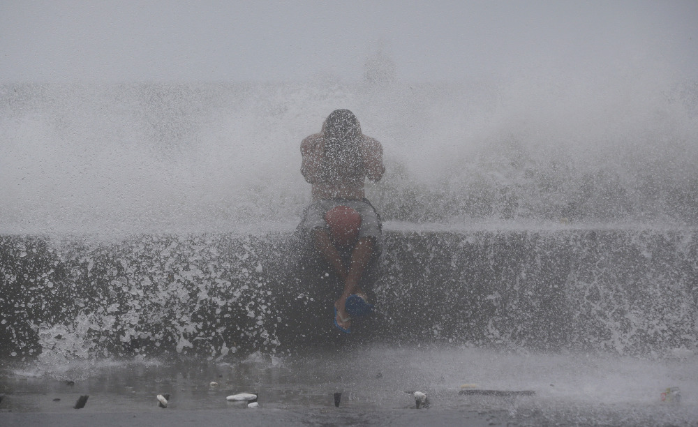 A Filipino reacts as he is hit by waves along a promenade in Manila, Philippines, on Sunday.