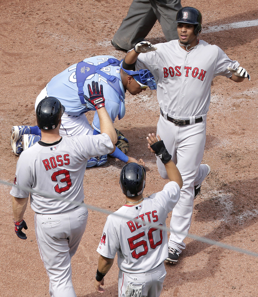 Boston Red Sox's Xander Bogaerts, right, is welcomed home by David Ross (3) and Mookie Betts (50) after hitting a three-run home run during the third inning of a baseball game against the Kansas City Royals Sunday.