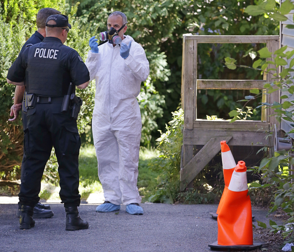 An exterminator, right, talks with a Blackstone police officer standing post and a member of the inspections services division of the Blackstone health department before entering through the back door of a house in Blackstone, Mass. on Friday where a prosecutor said the bodies of three infants were found earlier in the week.