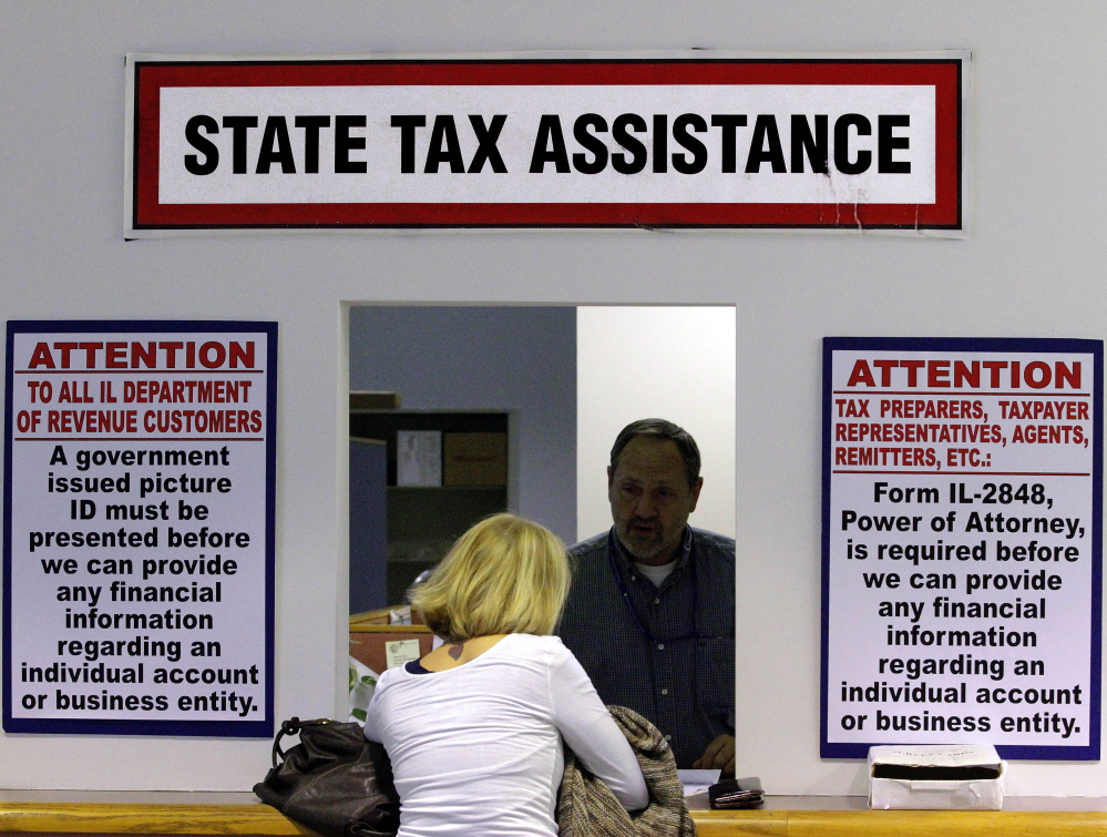 In this April 16, 2012 file photo, an Illinois Department of Revenue employee offers assistance to income tax payers at the Illinois Department of Revenue in Springfield, Ill. The widening gap between the wealthiest Americans and everyone else has been matched by a slowdown in state tax revenue, according to a report being released Monday by Standard & Poor's.