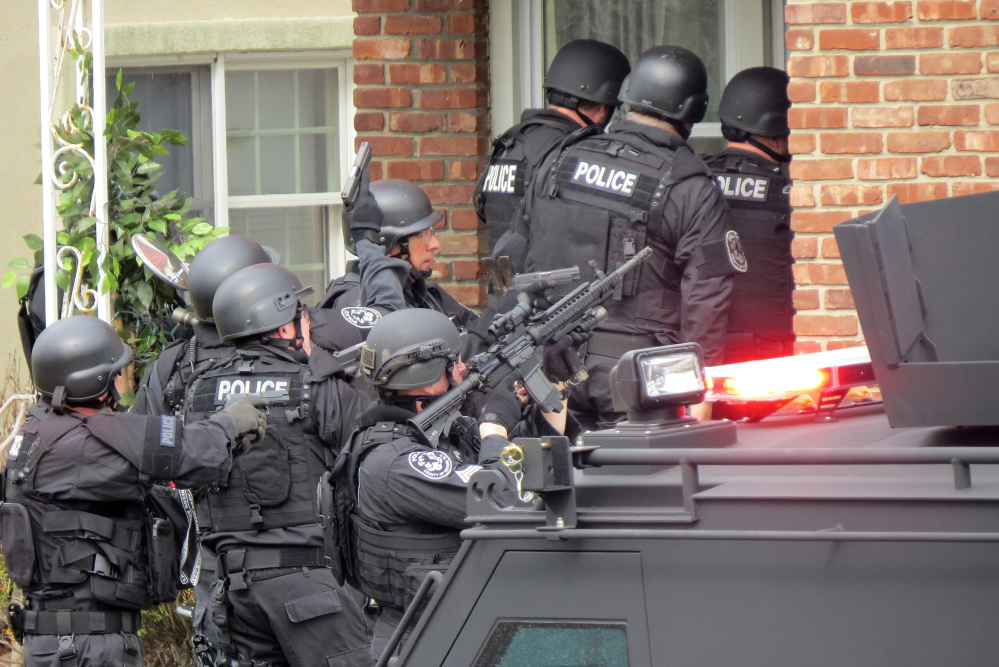 Nassau County police officers enter a home in Long Beach, N.Y., in April in search of an armed killer, based on a phone call that turned out to be a hoax that cost the department $100,000.