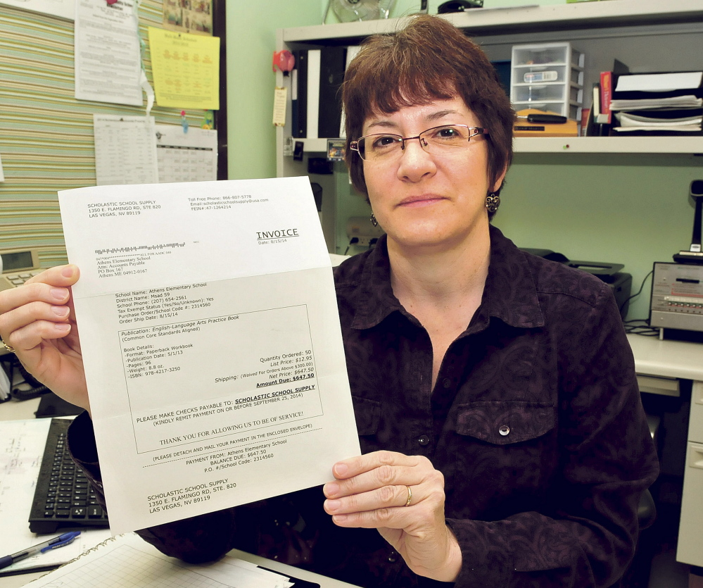 Athens Community School Administrative Assistant Nancy Martin holds the original invoice for books that the school was billed for but did not order.
