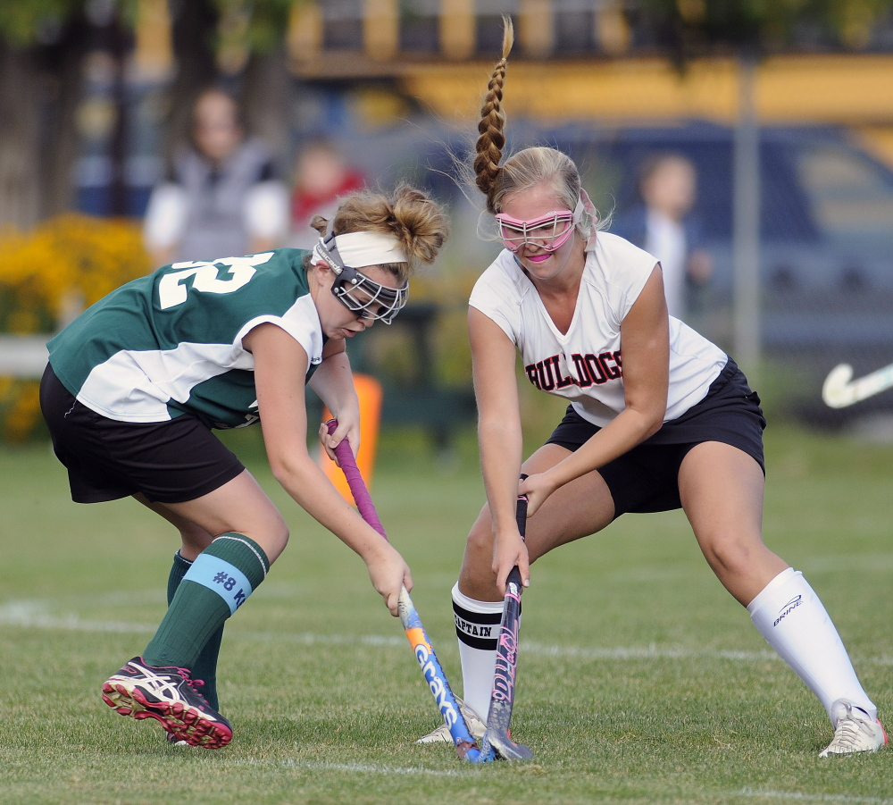 Hall-Dale High School's Nicole Pelletier, right, and Winthrop High School's Kat Hajduk try to gain control of the ball Monday in Farmingdale.