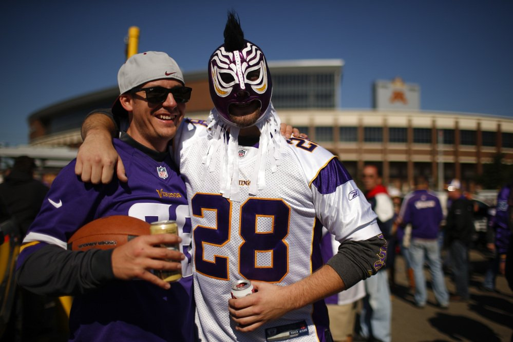 Two fans tailgate outside TCF Bank Stadium wearing Adrian Peterson jerseys before the start of a game last Sunday between the Minnesota Vikings and the New England Patriots in Minneapolis. Peterson was indicted in Texas last week for using a branch to spank one of his sons. He turned himself in at a jail in Montgomery County, was processed and released, and deactivated by the Vikings. He was reactivated by the team Monday.