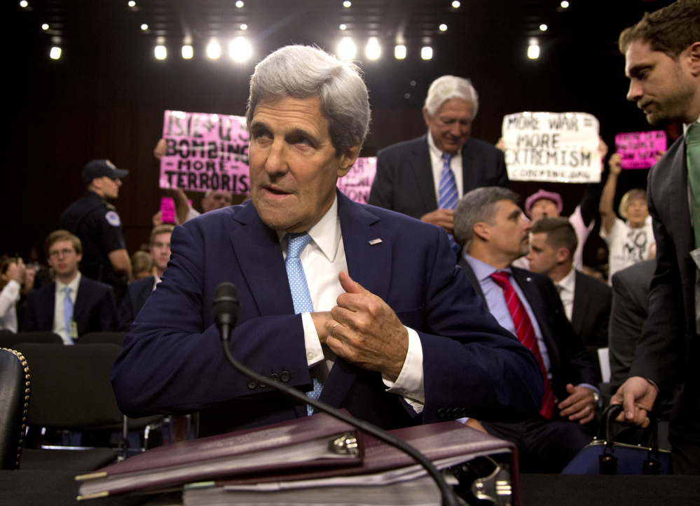 As protesters from CodePink hold up signs and shout behind him, Secretary of State John Kerry settles into his seat as he arrives to testify on Capitol Hill in Washington on Wednesday during a Senate Foreign Relations Committee hearing on the U.S. strategy to defeat the Islamic State group.