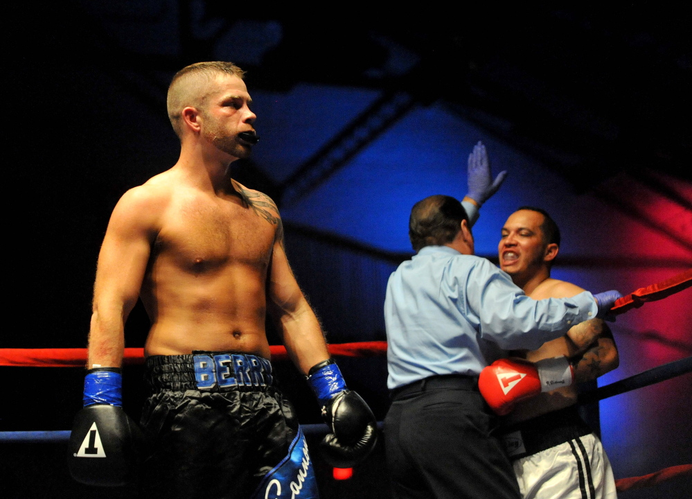 The referee calls the fight after light welterweight fighter Brandon Berry, left, scored a TKO against Moises Rivera in the second round of a fight at the Portland Expo on June 14.