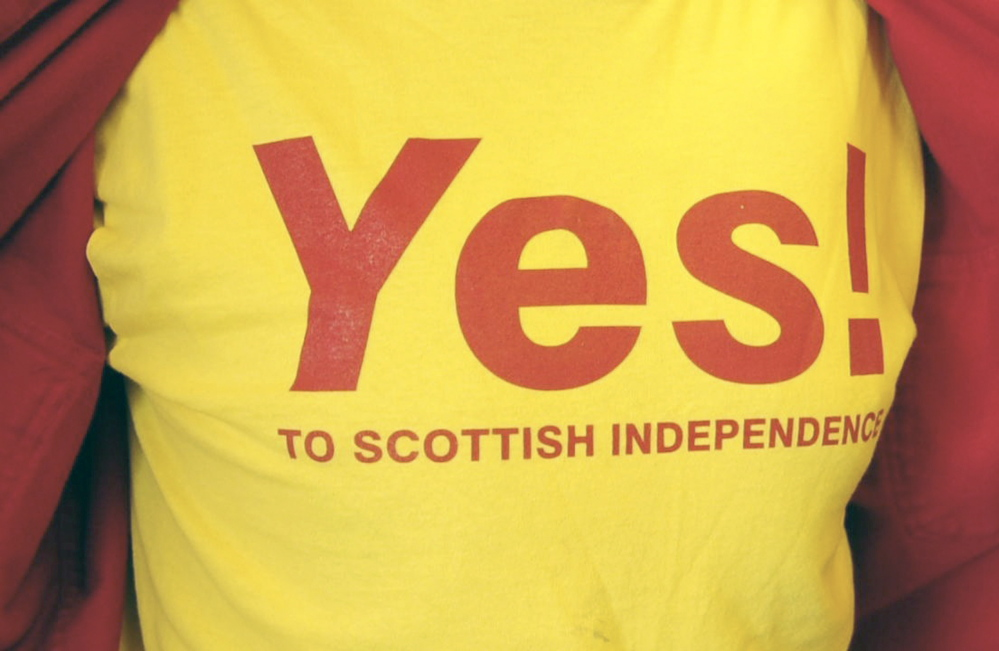 Bill McKeen shows off the T-shirt he made saying yes to Scottish independence during an interview on Tuesday at Minuteman Signs in Augusta.