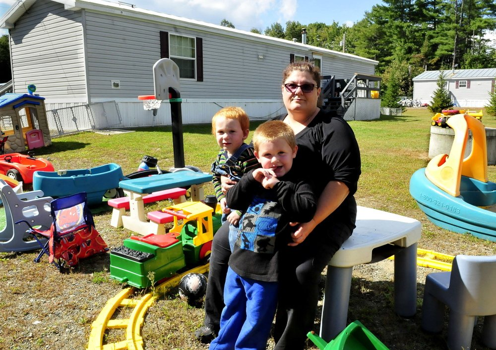 Dawn Zammuto with her grandsons Allen, left, and Dominic outside the home she rents in Norridgewock on Wednesday. Zammuto is facing an eviction hearing requested by her landlord because he says she violated a no pet rule after she allowed her daughter Jessica Botto and her service dog to stay five days in August.