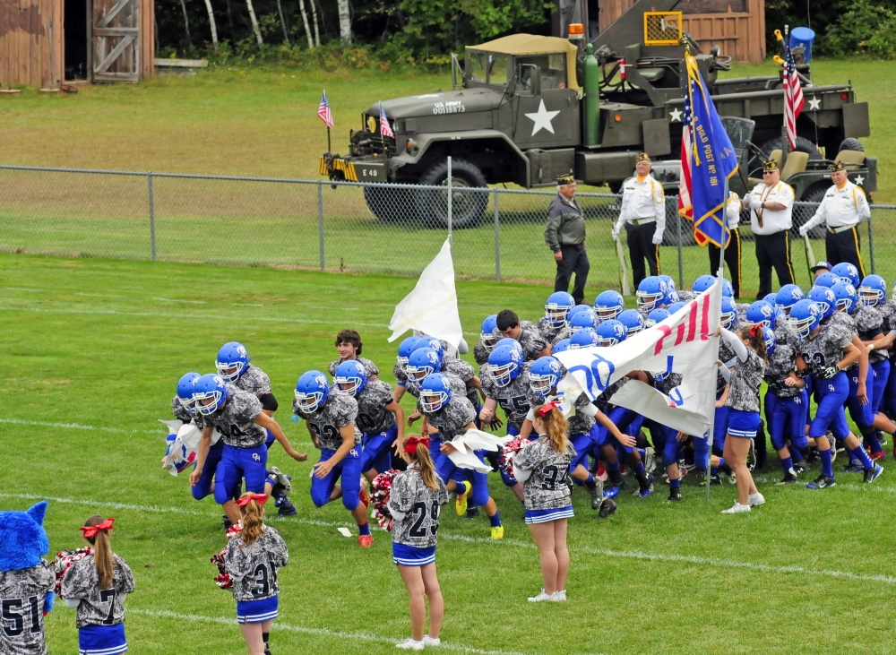 Members of the Oak Hill football team take the field in their camouflage uniforms before a game Saturday against Dirigo.