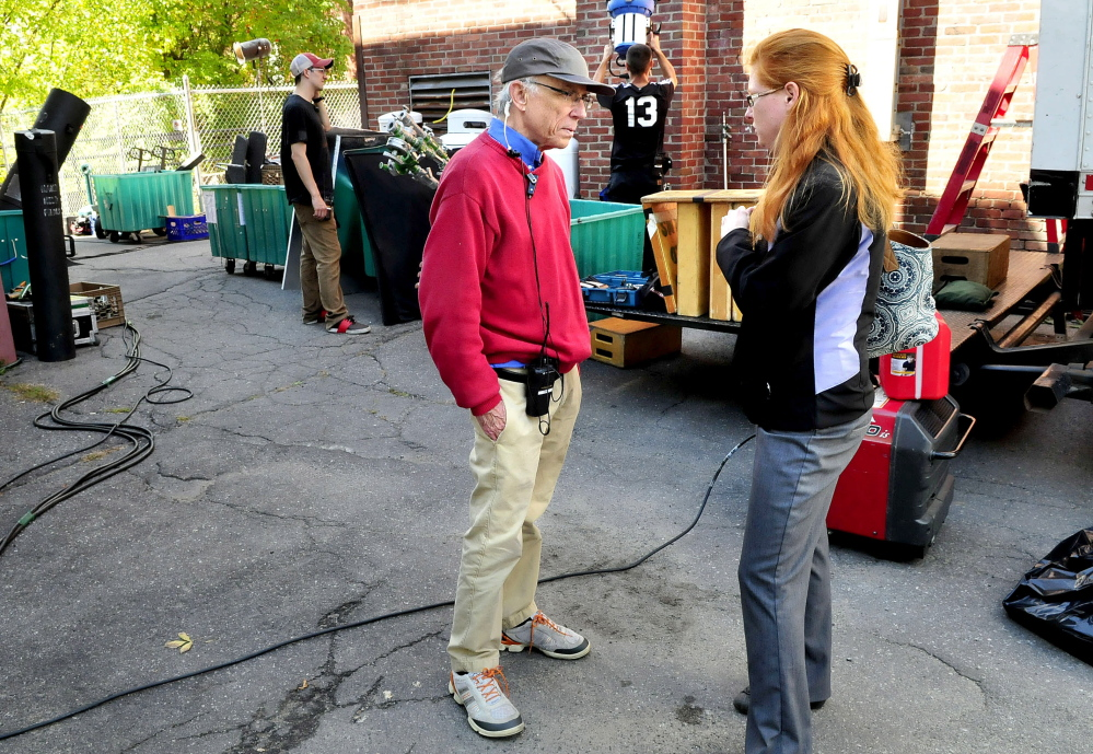 "Unit production manager Kip Kippax and Skowhegan Town Manager Christine Almand speak outside the Old Mill Pub in Skowhegan on Wednesday as workers bring equipment into the tavern to film promotional commercials for ""American Pickers"" and ""Down East Dickering."""