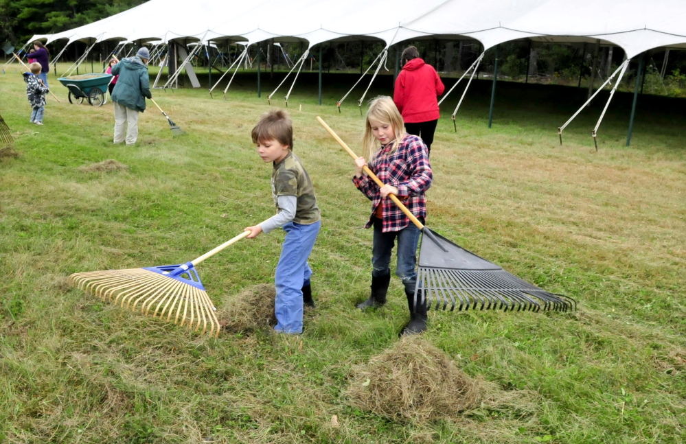 Volunteers Forest Pitkin and Juniper Fowler on Tuesday help rake mowed grass outside a vendor tent while preparing for the three-day Common Ground Country Fair that begins this Friday in Unity.