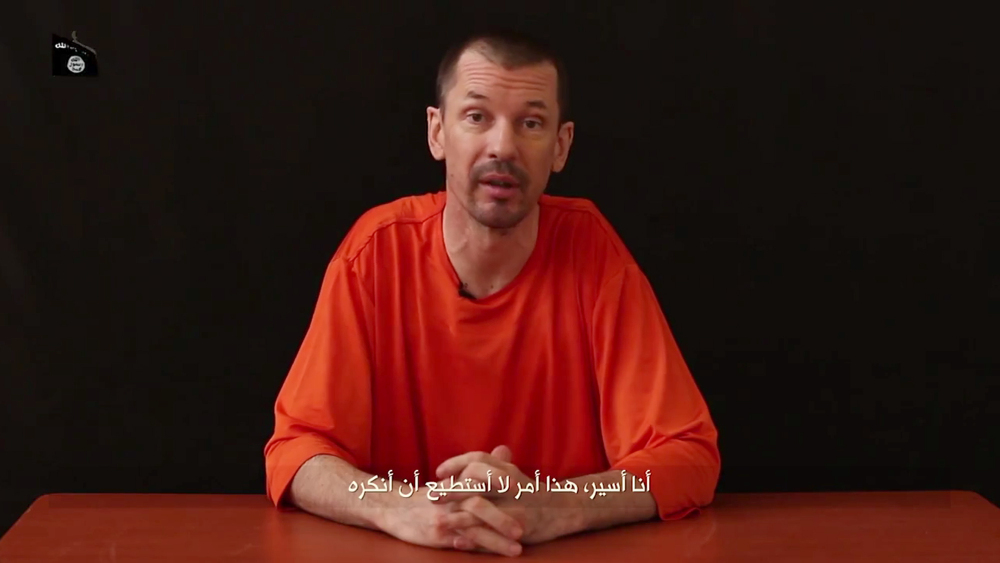"In this still image taken from an undated video published on the Internet by Al-Furqan, the media arm of the Islamic State group militants, captive British journalist John Cantlie speaks into the camera on the first of what he says will be a series of lecture-like ""programs"" in which he says he will reveal ""the truth"" about the Islamic State group. The Arabic subtitle reads ""I am a prisoner and that is something I will not deny."""