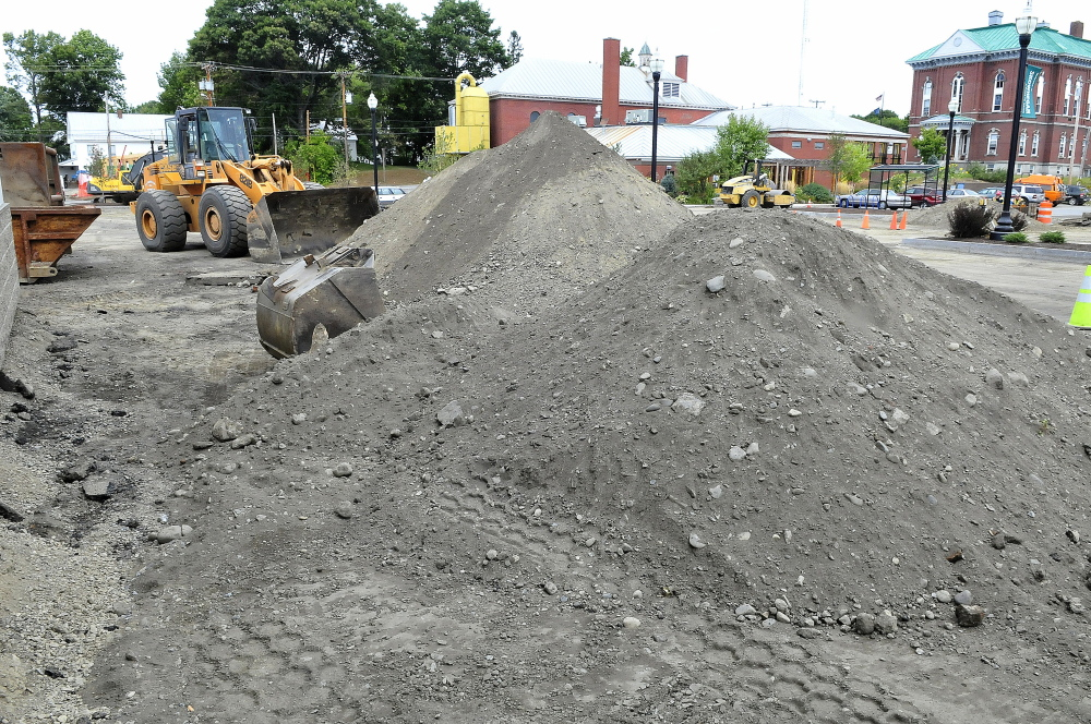 Contractors prepare to resurface the municipal parking lot in Skowhegan. The remains of a building and other debris near the piles of gravel were exposed during work behind the Hight car dealership.