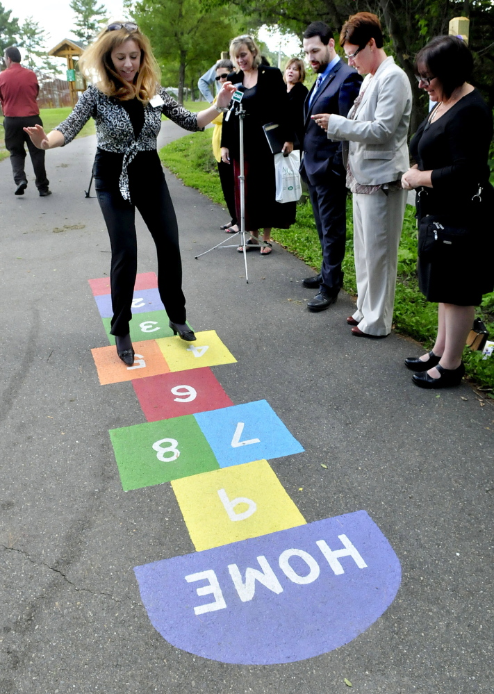 Tina Chapman of the Waterville Rotary Club is cheered on as she demonstrates hopscotch, one of 10 stations along a walking trail in Waterville, during a press conference on Thursday to bring attention to the trail system and encourage parents and children to use.
