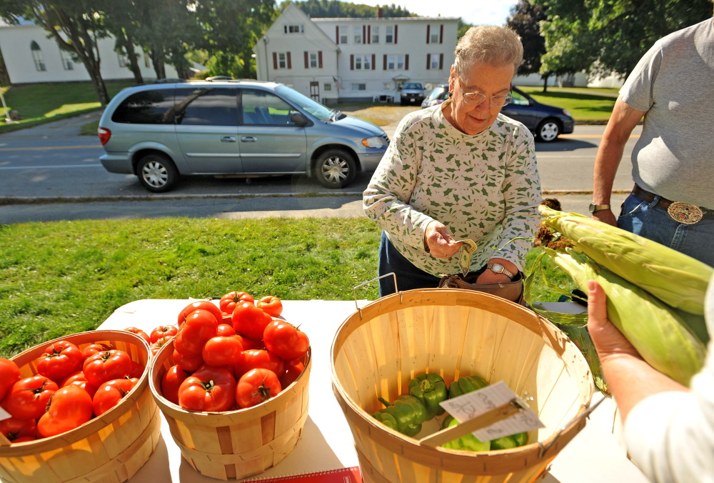 Mary Wade buys corn at the farm stand on Main Street in Bingham on Thursday. The Good Shepherd Food Bank in collaboration with Maine Federation of Farmers' Markets created the farm stand to offer discounted produce in rural Maine, where farmers markets can be impractical.