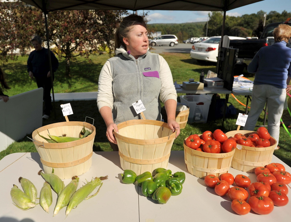 Meghan Quinn, an intern with the Good Shepherd Food Bank, manages the farm stand on Main Street in Bingham on Thursday. The farm stand offers discounted produce and accepts EBT cards.
