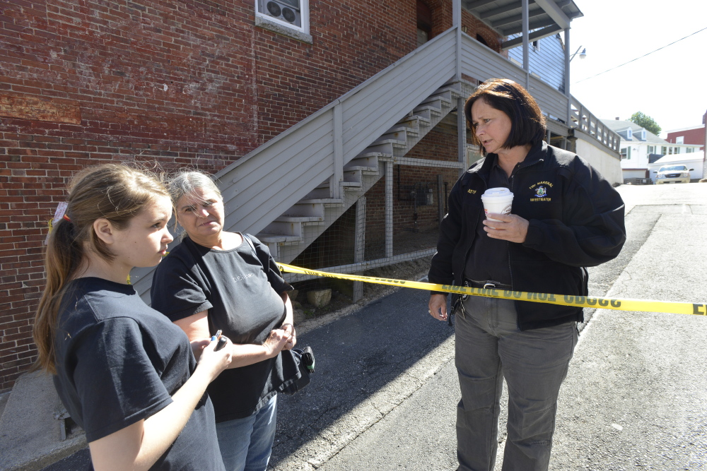 Fire victim Carrie Chenery, center, and granddaughter Keauna Froehlich, 14, talk with state fire investigator Mary MacMaster on Friday as they and other residents try to reclaim personal items from their apartments in Biddeford.