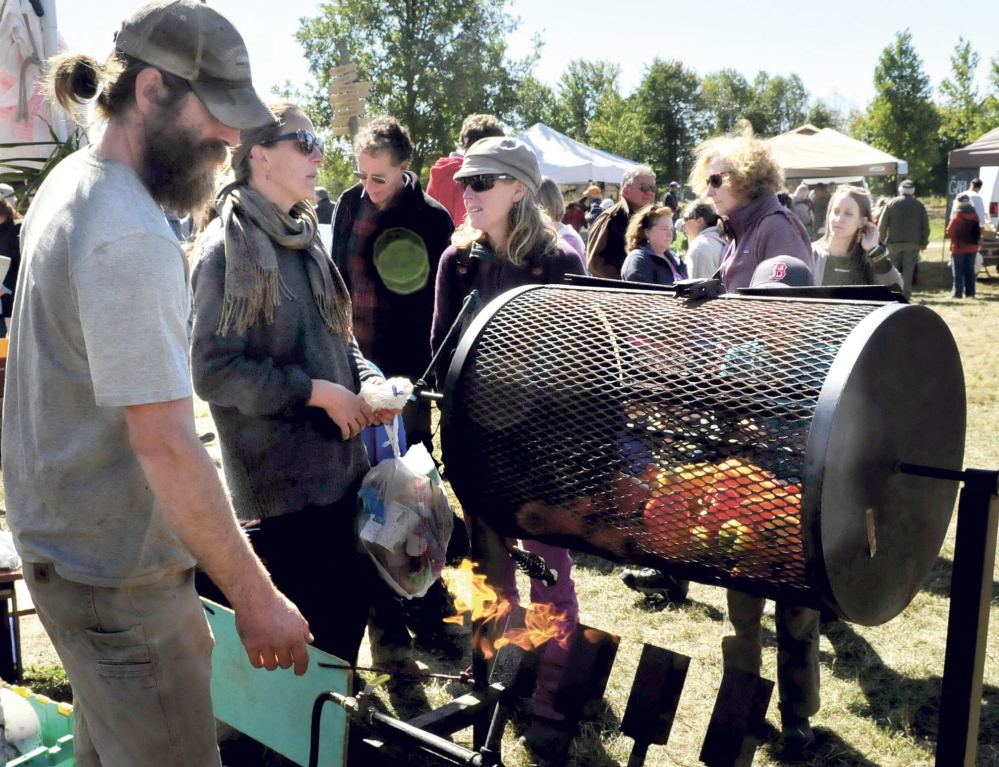 Dan Price of Freedom Farm demonstrates roasting peppers  in a gas — heated rotisserie to curious onlookers during the three-day Common Ground Country Fair in Unity, which opened Friday.