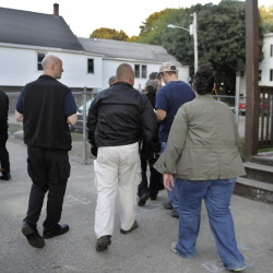 Federal, state, county and corrections officers descend Thursday upon an apartment in Augusta while assisting the city's police in checking on a resident on probation during a coordinated sweep through the community.