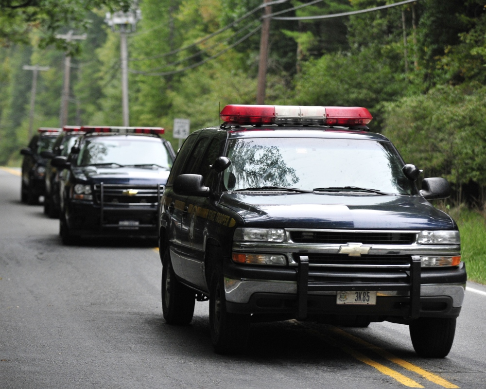 Police surround a neighborhood in the Pocono Mountains in search of suspect Eric Frein on Saturday in Canandensis, Pa. Police have charged Frein with opening fire outside a state police barracks in northeastern Pennsylvania on Sept. 12. Cpl. Bryon Dickson was killed and Trooper Alex Douglass was wounded by the gunman with a high-powered rifle.