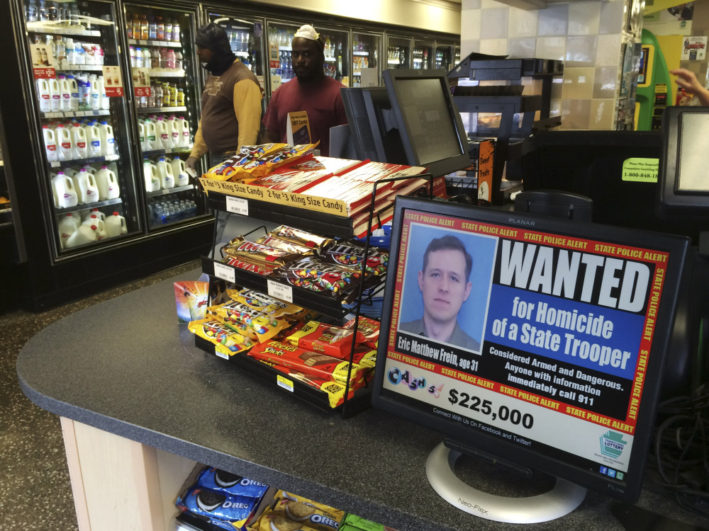 A video display at a convenience store shows a wanted poster of Eric Frein, a 31-year-old from Canadensis, Pa., in Philadelphia. Frein is charged with killing Pennsylvania State Trooper Cpl. Bryon Dickson and wounding Trooper Alex Douglass in a late-night ambush Sept. 12 outside the Blooming Grove state police barracks.