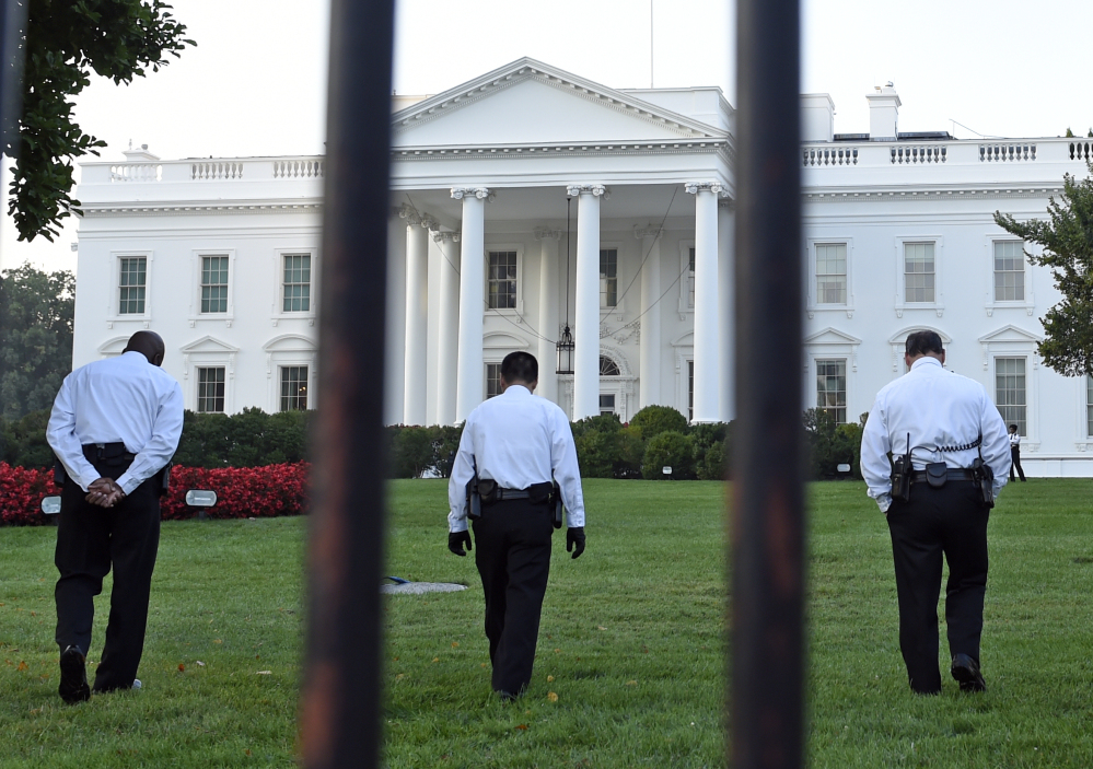 Uniformed Secret Service officers walk along the lawn on the North side of the White House in Washington on Saturday. The Secret Service is coming under renewed scrutiny after a man scaled the White House fence and made it all the way through the front door before he was apprehended.