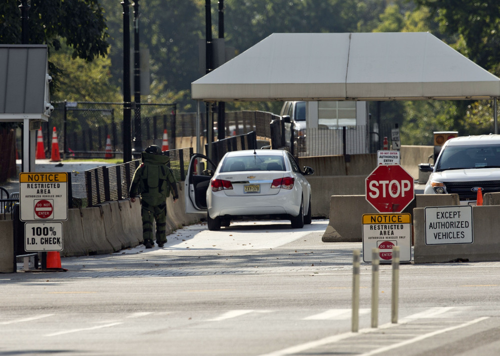 An explosive technician in a bomb suit approaches a vehicle near the entrance to White House in Washington, Saturday.