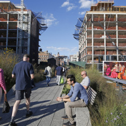 Pedestrians stroll along the High Line in New York as it winds between two buildings under construction. The last stretch of the elevated walkway opens to the public Sunday.