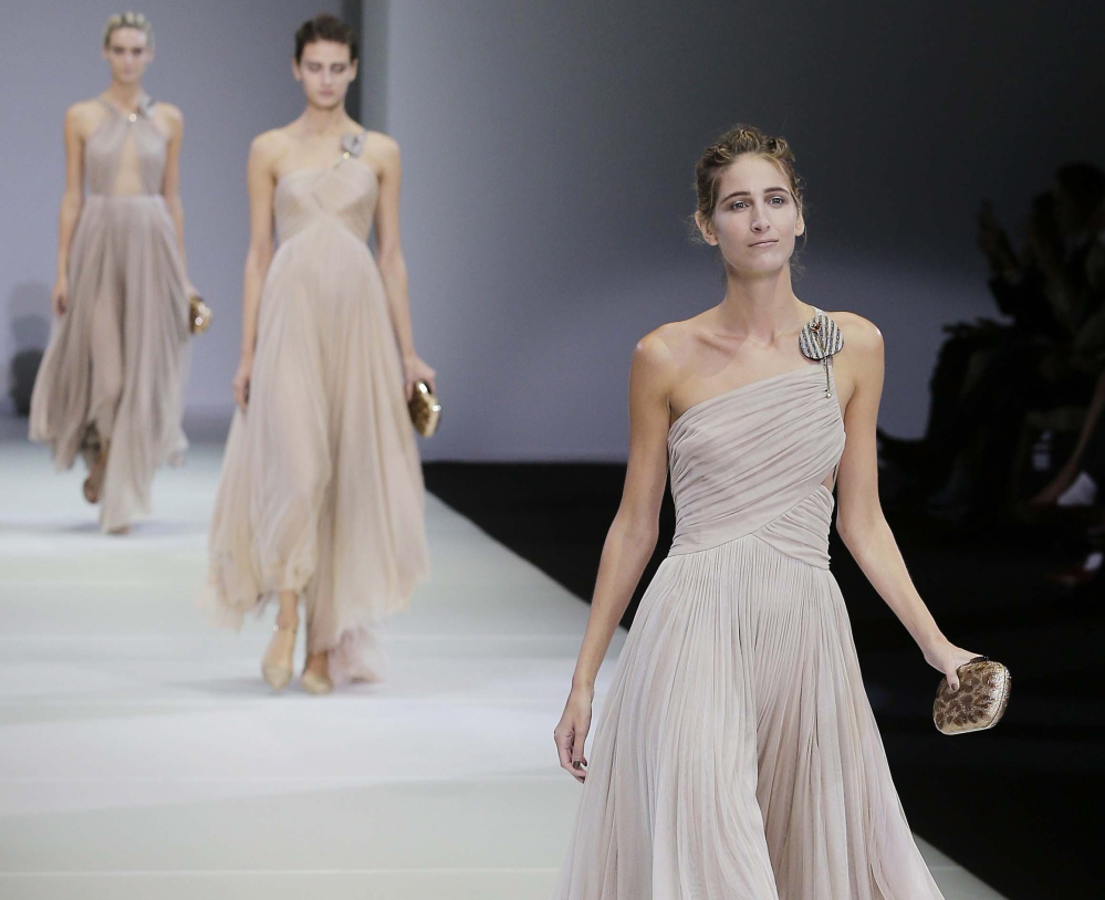 Models wear creations for Giorgio Armani women's Spring Summer 2015 collection, part of the Milan Fashion Week, unveiled in Milan, Italy, on Saturday.