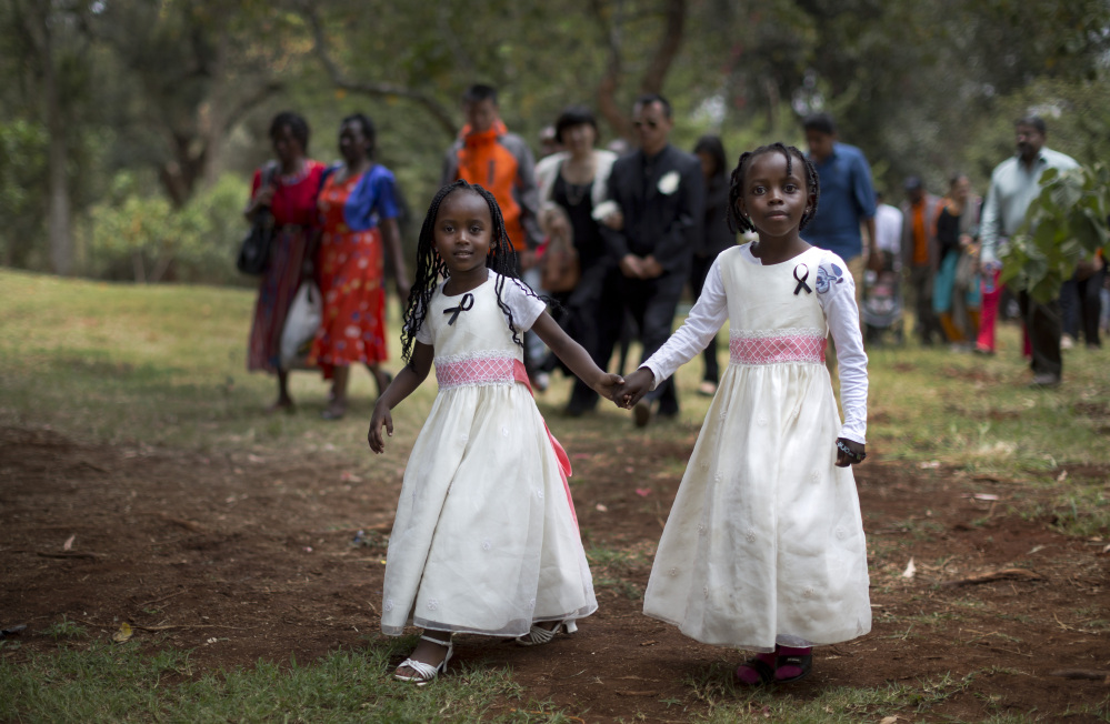 Gloria, 4, left, whose father, Christopher Chewa, was killed in the Westgate Mall attack, walks with her cousin, Miriam, 6, and other families of the victims to lay flowers and remember at the Amani Garden memorial site in the Karura Forest in Nairobi, Kenya on Sunday. Kenya is marking one year since four gunmen stormed the upscale Westgate Mall in Nairobi, killing 67 people.