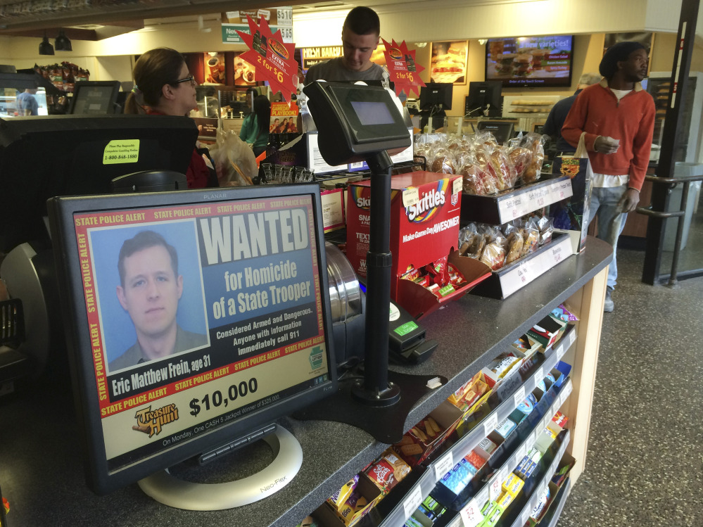 A video display at a convenience store shows a wanted poster of Eric Frein, a 31-year-old from Canadensis, Pa., Friday, in Philadelphia.