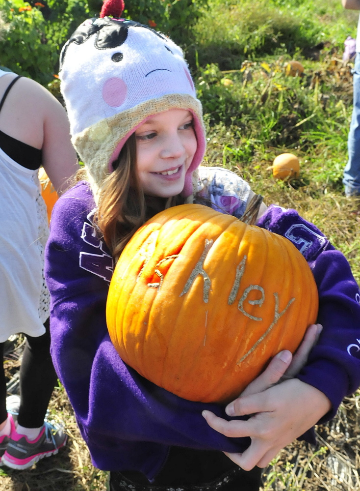 Albert S. Hall school student Ashley Harwood holds her pumpkin engraved with her name on Thursday after she and her fellow students donated onions to the Mid-Maine Homeless Shelter.