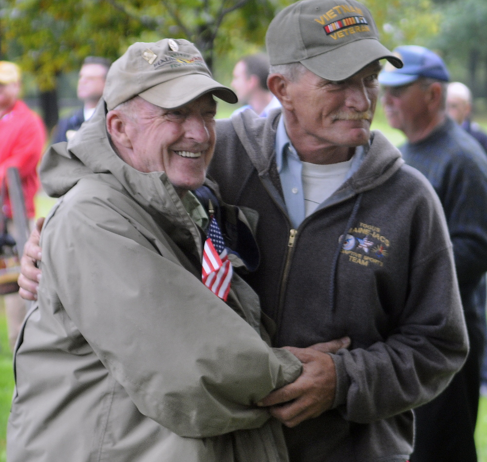 Vietnam veteran David Nevedomsky of Winslow, right, greets fellow veteran Don Taylor of Mount Vernon Sunday during a ceremony in Capitol Park in Augusta to honor Vietnam vets.