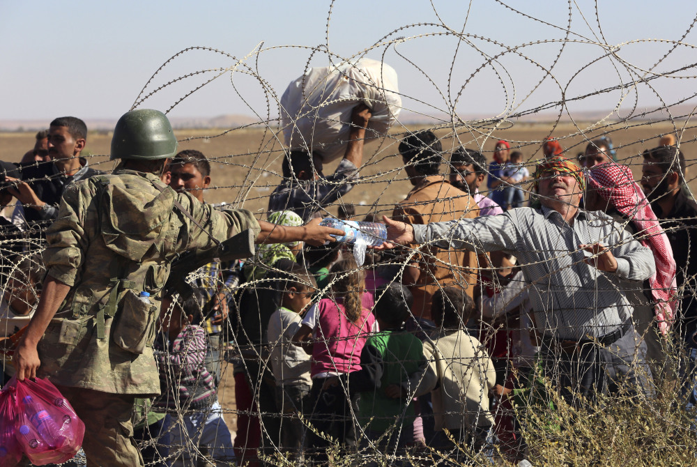 A Turkish soldier gives a bottle of water to a handicapped Syrian refugee waiting at the border in Suruc, Turkey, Sunday. Turkey opened its border Saturday to allow in up to 60,000 people who massed on the Turkey-Syria border, fleeing the Islamic militants' advance on Kobani.