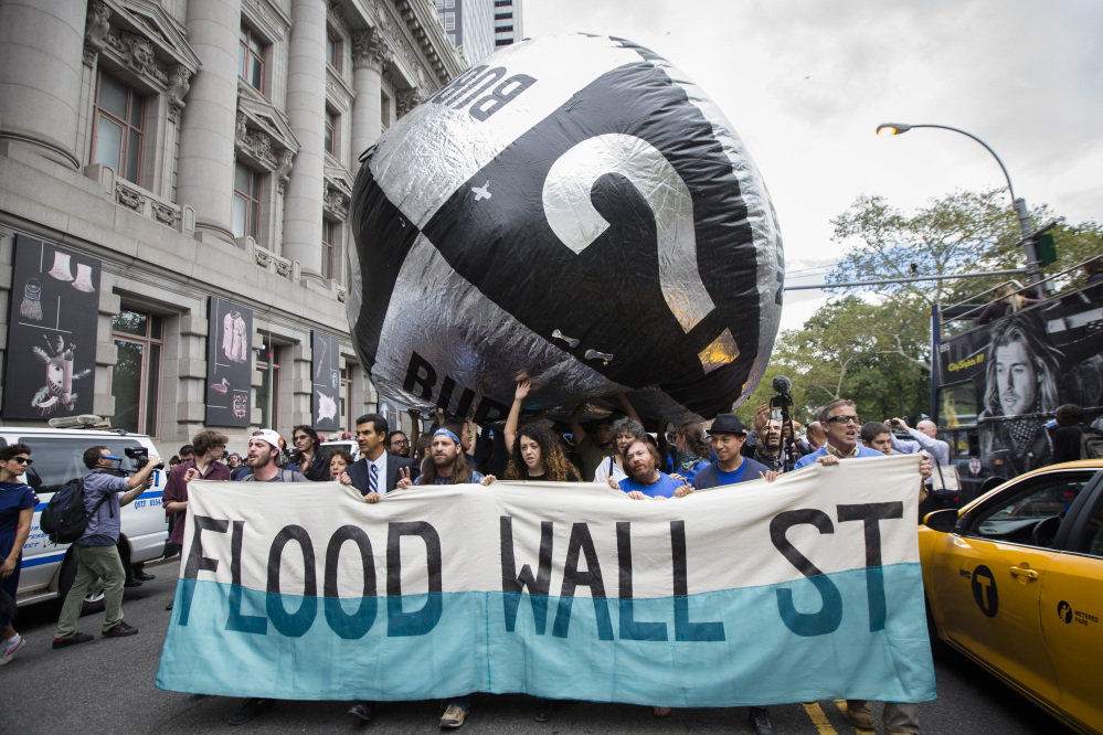 Demonstrators march towards Wall Street from Battery Park to protest for action on climate change and corporate greed Monday, a day after a huge climate march in New York City.