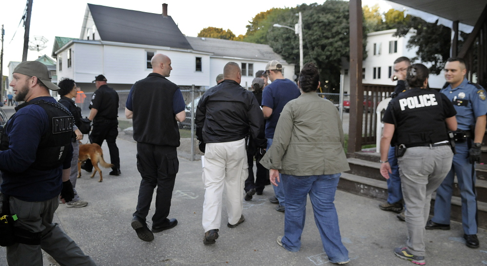Federal, state, county and corrections officers arrive at an apartment in Augusta Thursday while assisting the city's police in checking on a resident on probation during a coordinated sweep through the community.