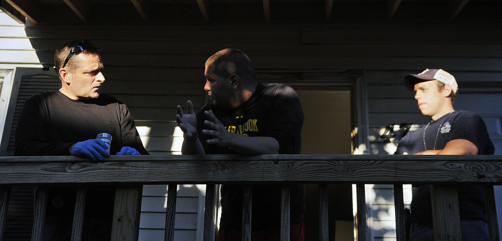 Probation Officer Mark Fortin, left, and Augusta Police Officer Ben Murtiff detain a parolee Thursday after searching his Augusta apartment during a sweep by several law enforcement agencies through the city.