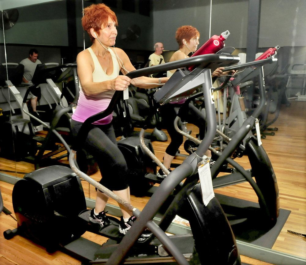 Carol Rowe is seen in a mirror while working out in the exercise room at Champions Fitness Center in Waterville on Monday.
