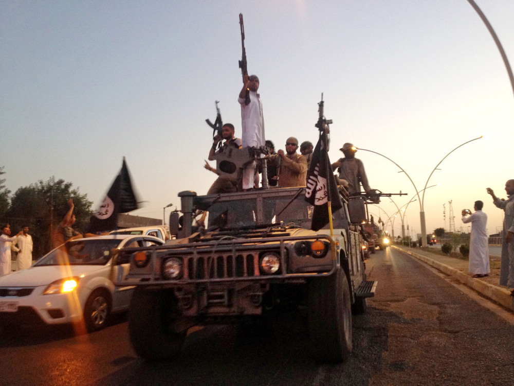 In this file photo taken Monday, June 23, 2014, fighters from the Islamic State group parade in a commandeered Iraqi security forces vehicle down a main road in the northern city of Mosul, Iraq.