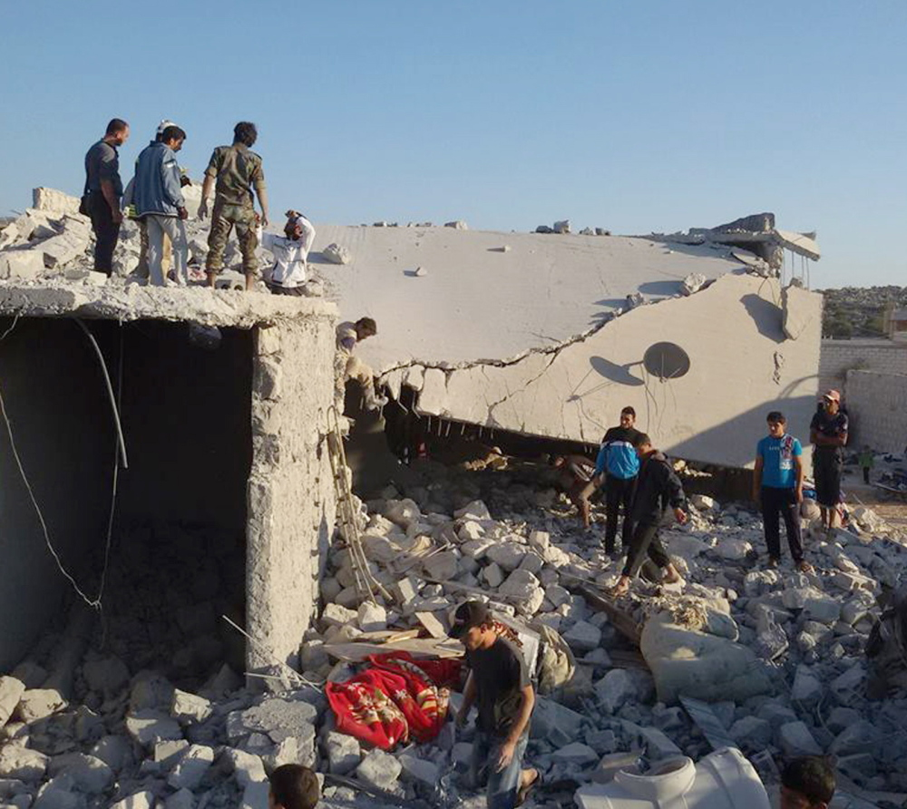 Syrians examine the rubble of a building in the village of Kfar Derian, Syria, that was leveled by coalition airstrikes during Tuesday's bombardment of Islamic State and Khorasan Group forces.